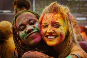 Two young women covered in paint hug.