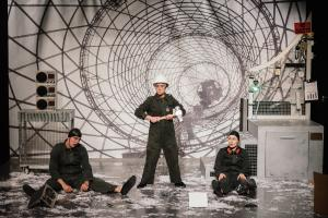 Three performers in boiler suits and hard hats appear on a stage, surrounded by technology