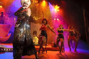 A drag performer sings on stage, backed by three female vocalists.