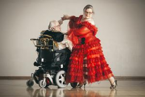 An elderly male wheelchair user dances with a female partner.