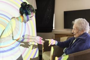 A performer from Spare Tyre Theatre Company, covered in a light projection, interacts with an elderly woman.