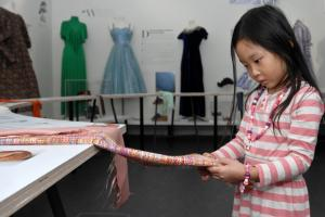 A young girl studies a piece of patterned fabric.