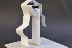 An abstract white paper sculpture - a pillar with paper folding gently from it.