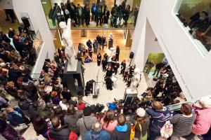 Musicians perform in atrium of Ashmolean Museum as crowds look on from above.