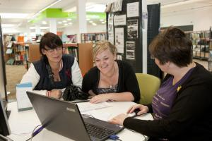 Three women gather around laptops in a library.