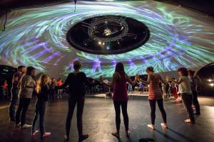 Participants standing in a circle hand to hand whilst abstract images are projected onto a dome above their heads.