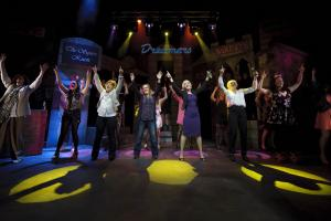 A large group of actresses hold their hands in the air in celebration on a stage designed to look like an Oldham street.