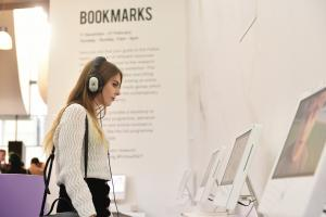 A woman looks at a video screen, wearing headphones, in a gallery space.