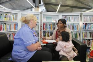 A nurse talks to a mother and child in a library.