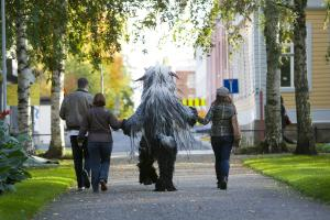Three people and a furry monster have there backs to us whilst walking down a path.