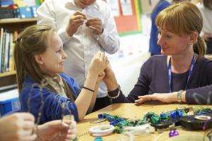 A young girl and a staff member at Shakespeare Week make jewelry together.