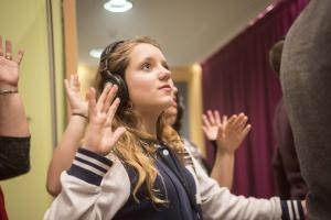 A teenage girl wearing headphones as part of an interactive theatre piece holds her hands in the air.