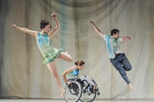 Three performers with disabilities from Stopgap Dance Company, including a wheelchair user, perform a dance piece.