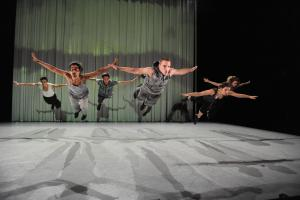 Six male dancers from Yasmin Vardimon Dance Company dive into the air and appear to be flying.