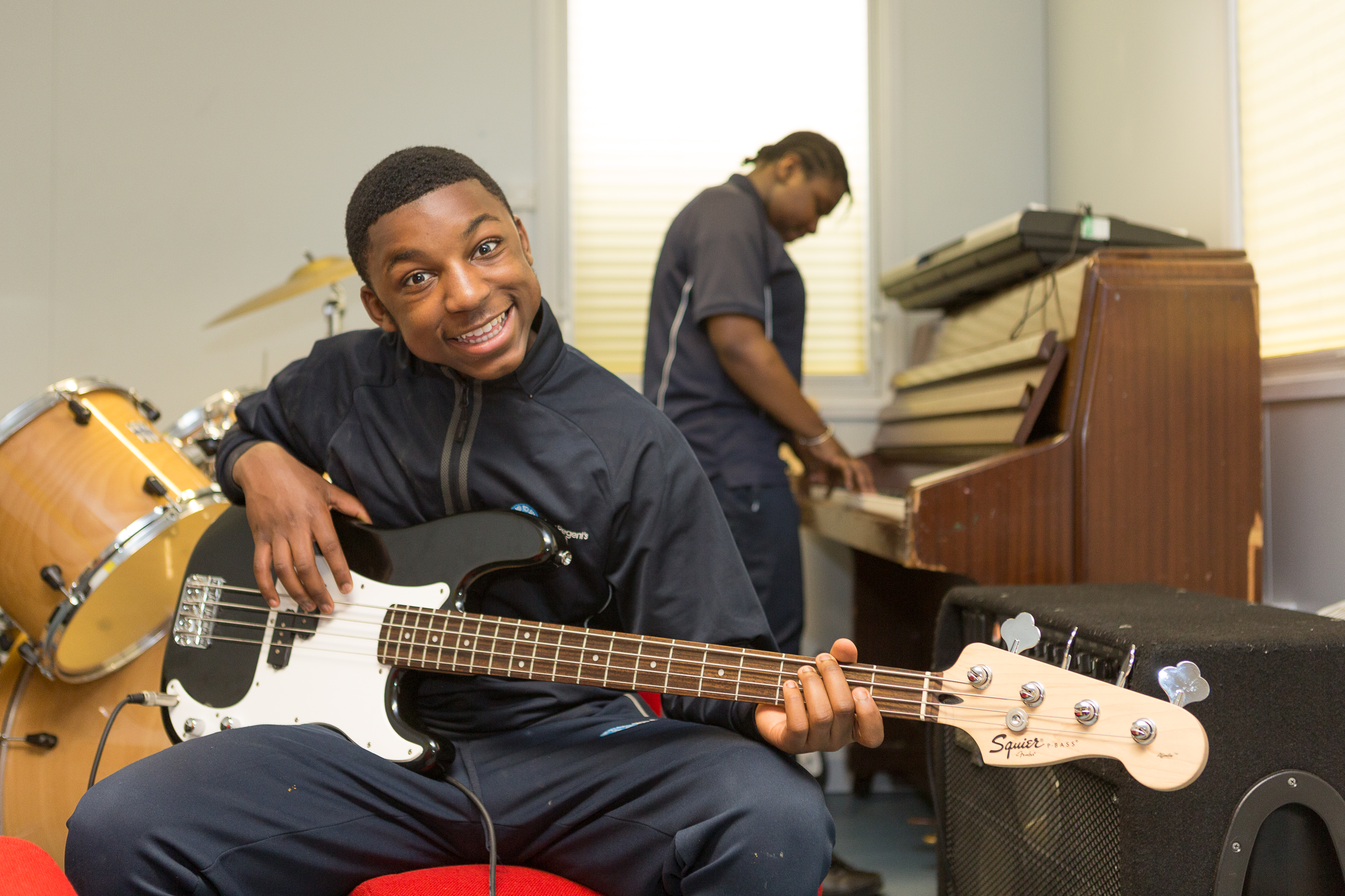 A young man smiles while playing bass guitar, as another plays piano in the background
