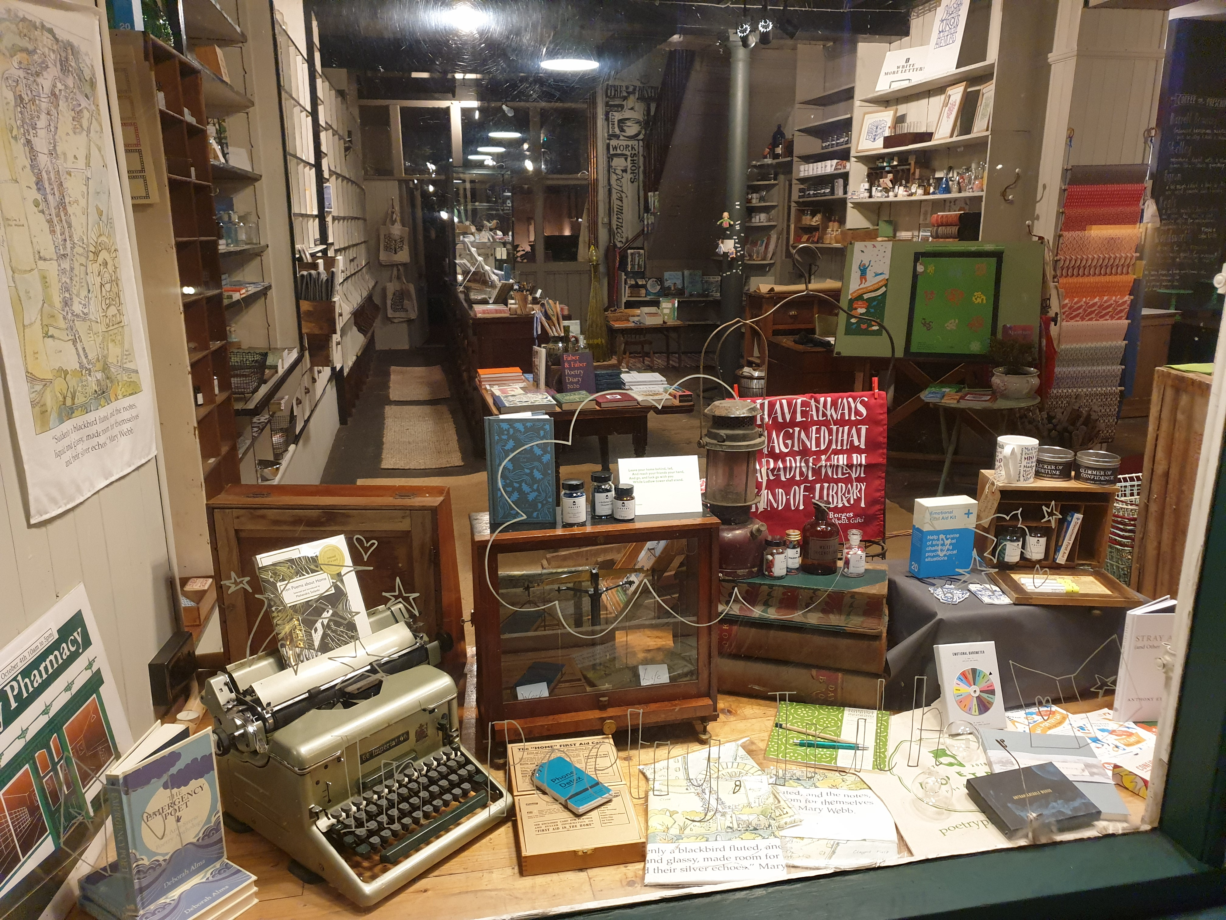 A view from the outside through the window of the Poetry Pharmacy. There is an old typewriter, shelves with bottles of ink, paper, books, boxes and drawers.