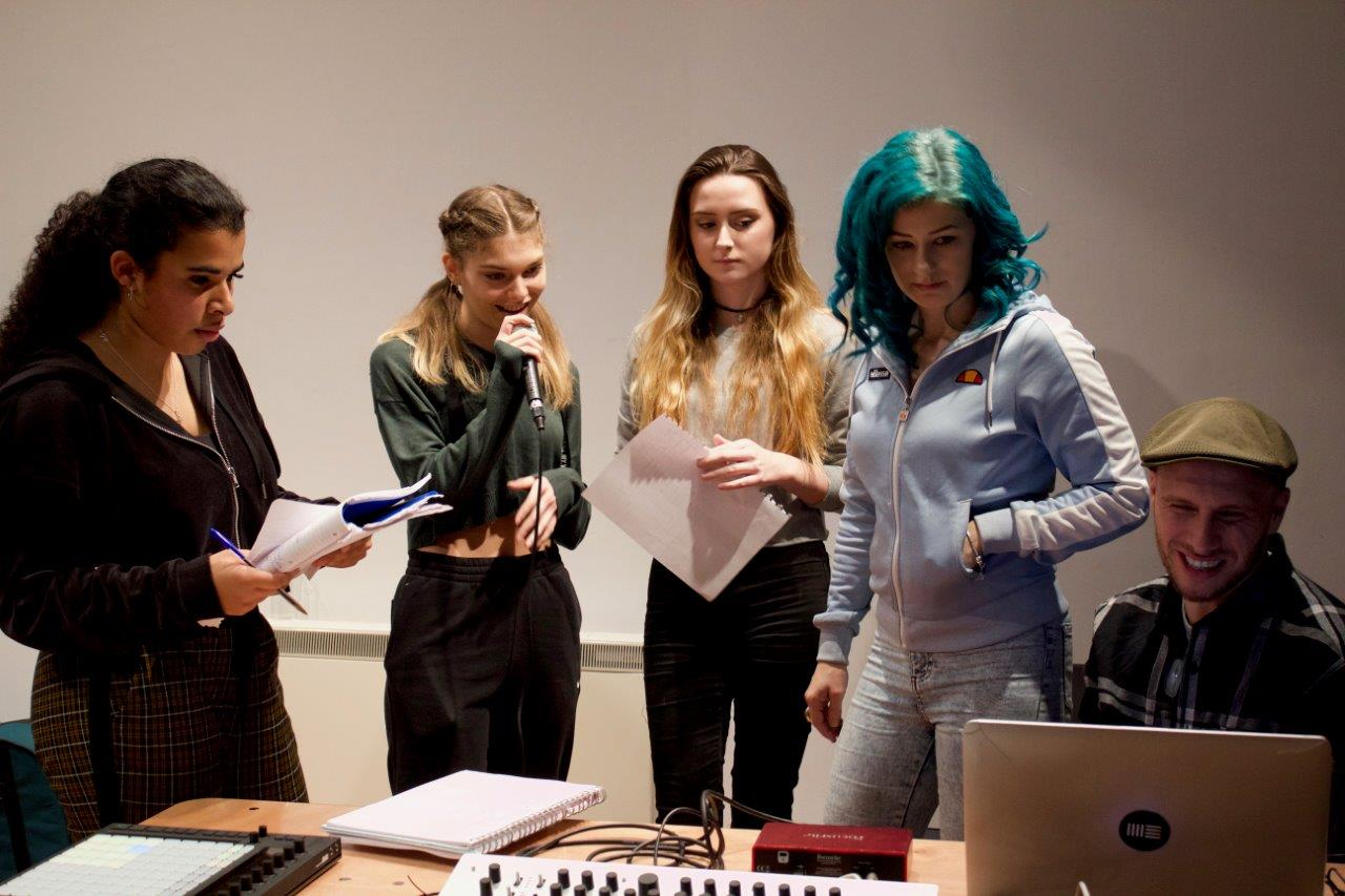 A group of young people are stood around a desk. One of the girls is holding a mic.