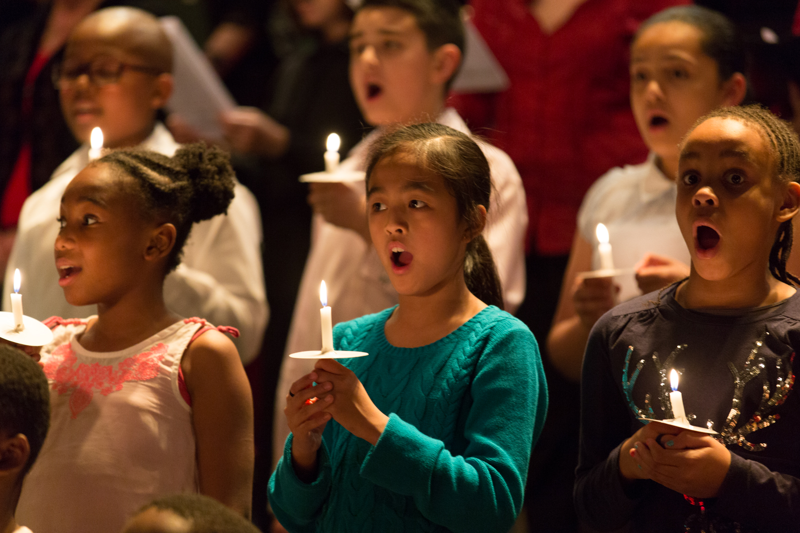 A row of young girls stand singing as part of a choir whilst holding candles