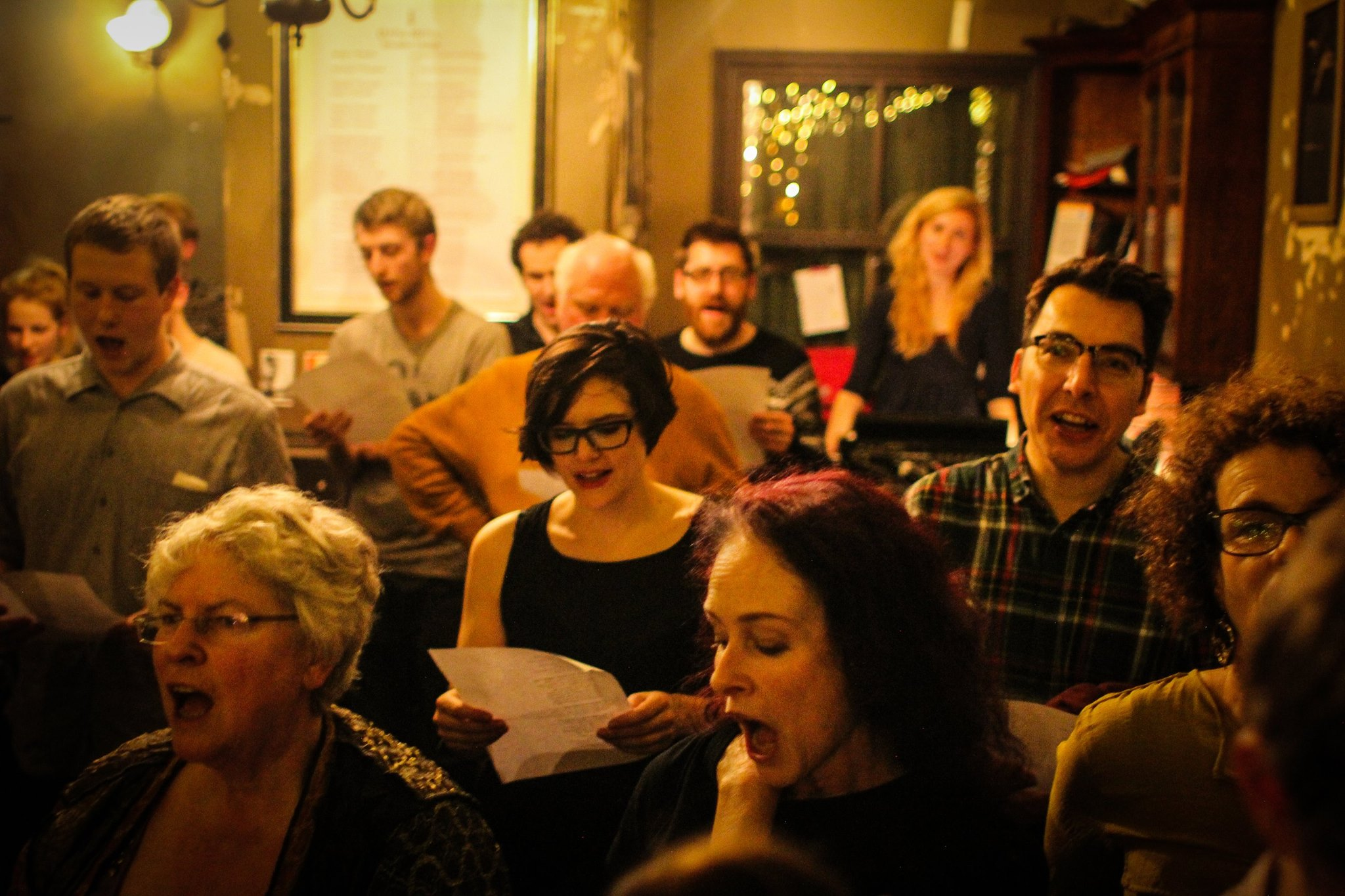 A group of people stand singing in a performance space in a pub holding hymn sheets