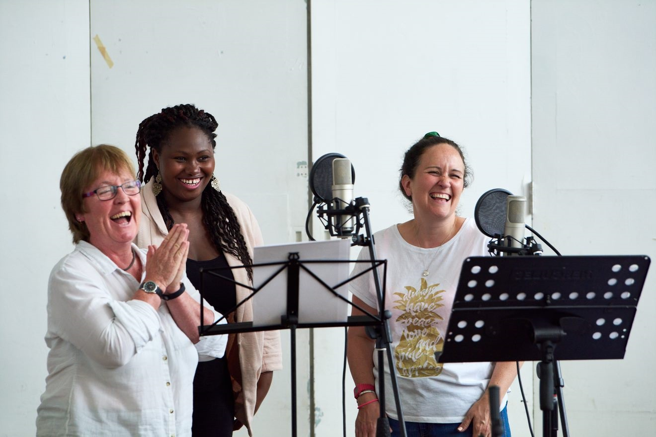 Three women are smiling and laughing at music stands and recording microphones
