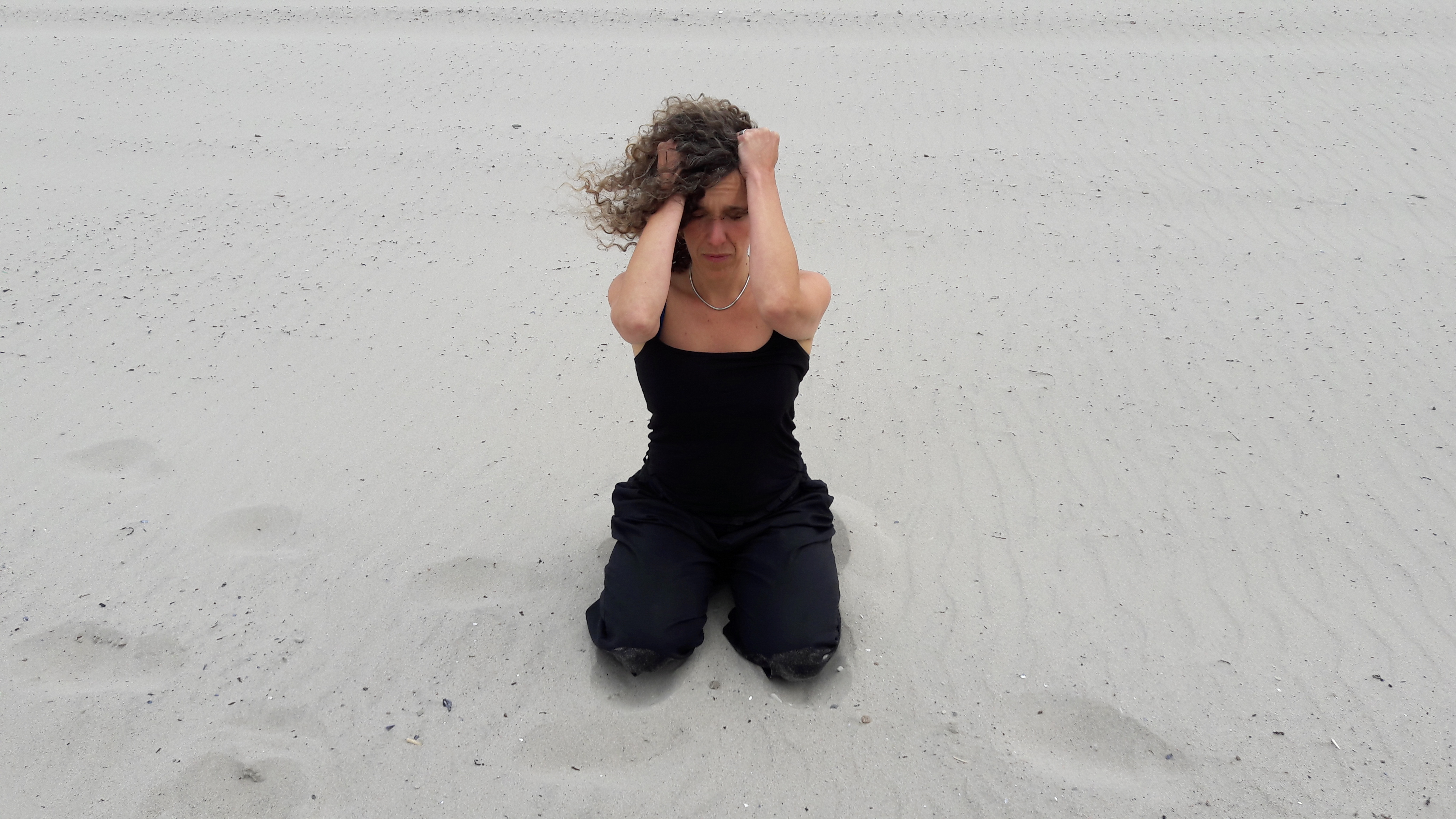 A women kneels on sand, dresses all in black, with her hands on her head in frustration