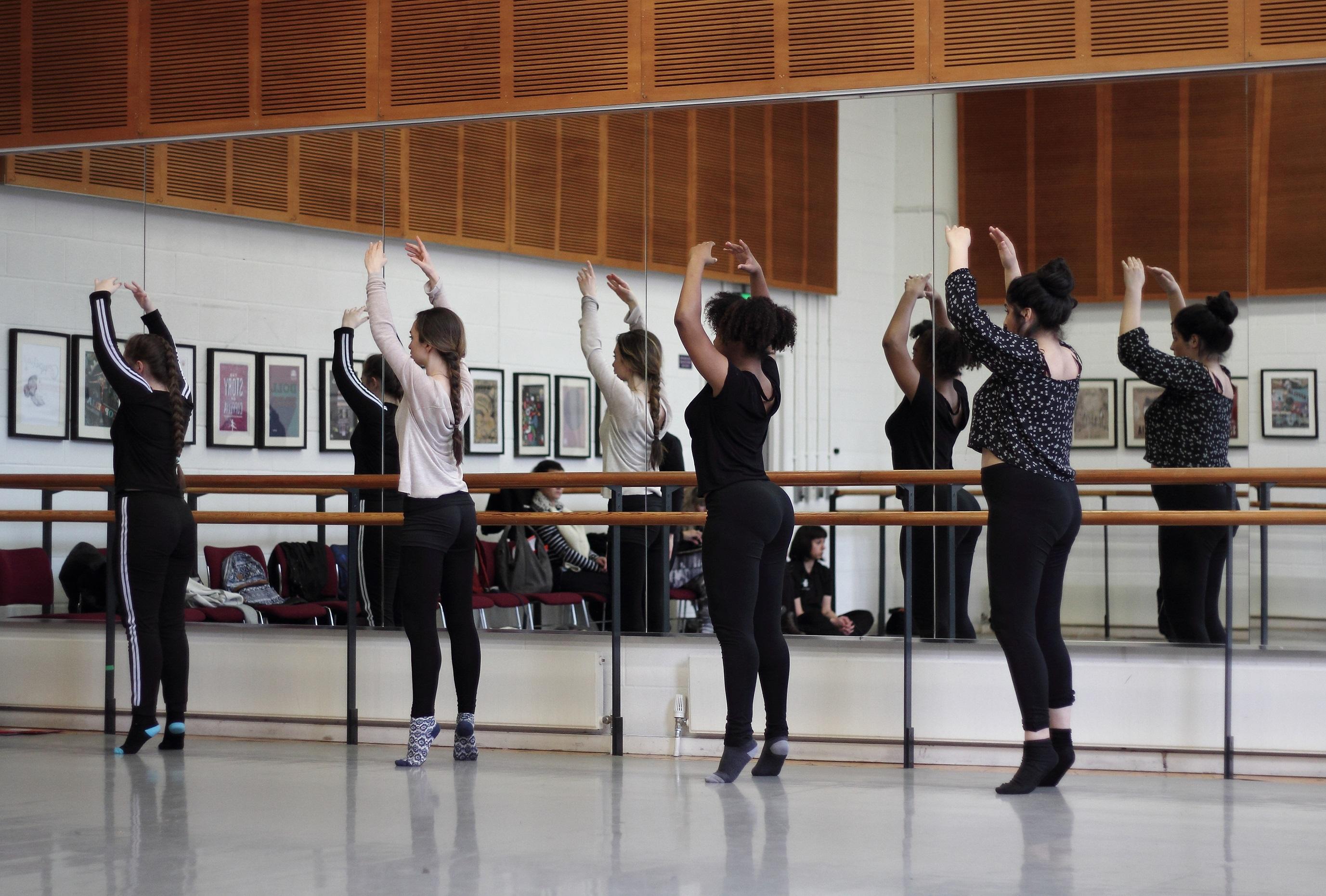 Four girls balance on a ballet bar