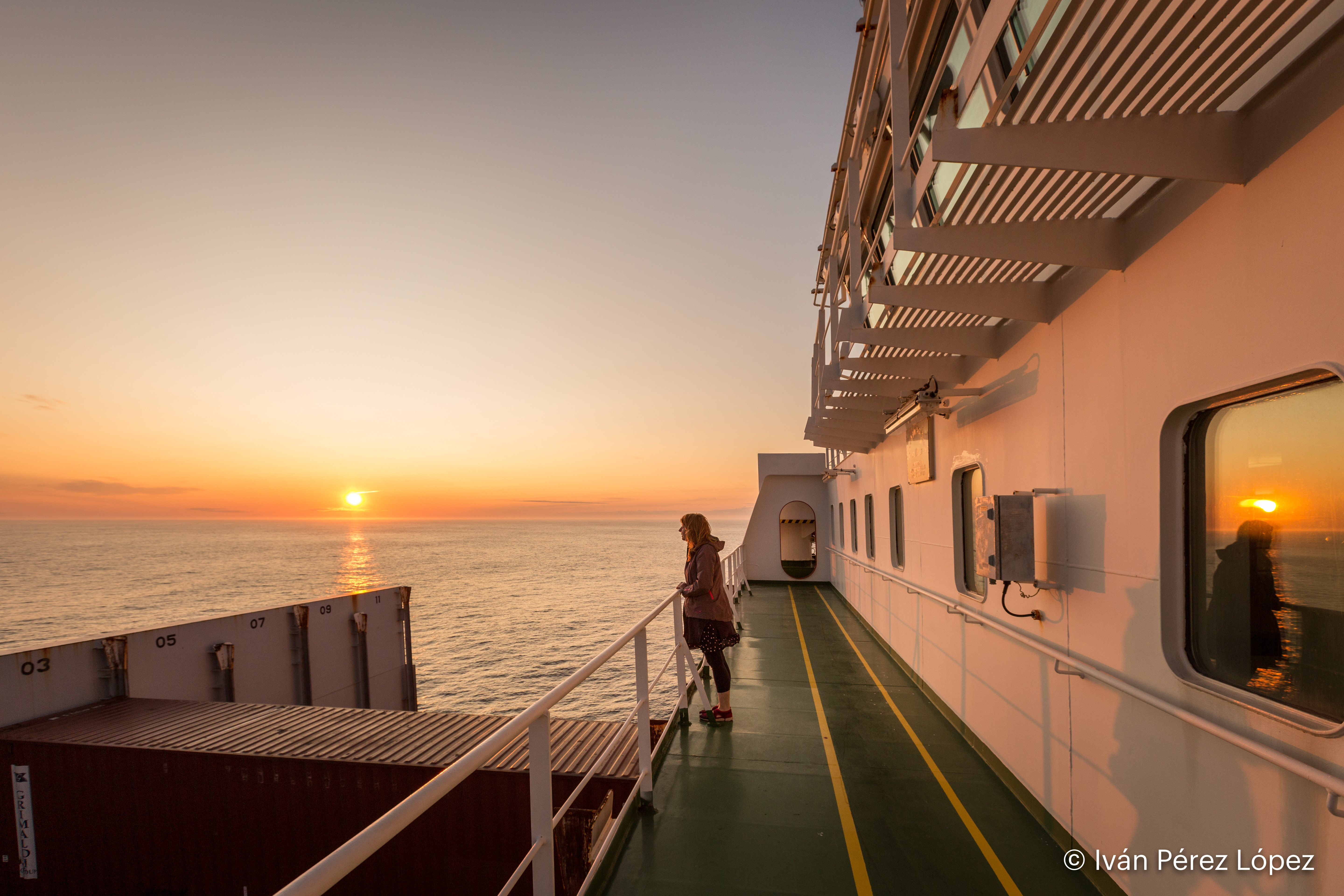 A woman stands on deck of a large ship, lookinhg out to sea. A sunset is beihnd her.