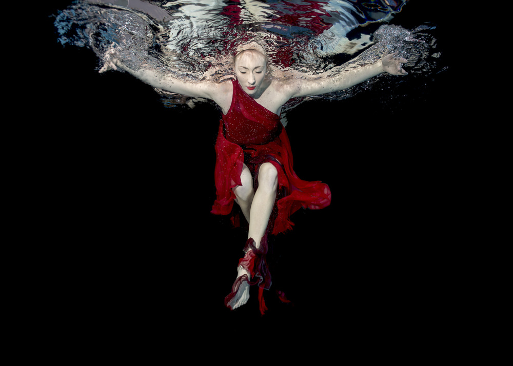 Underwater photograph of a lady in a red dress.