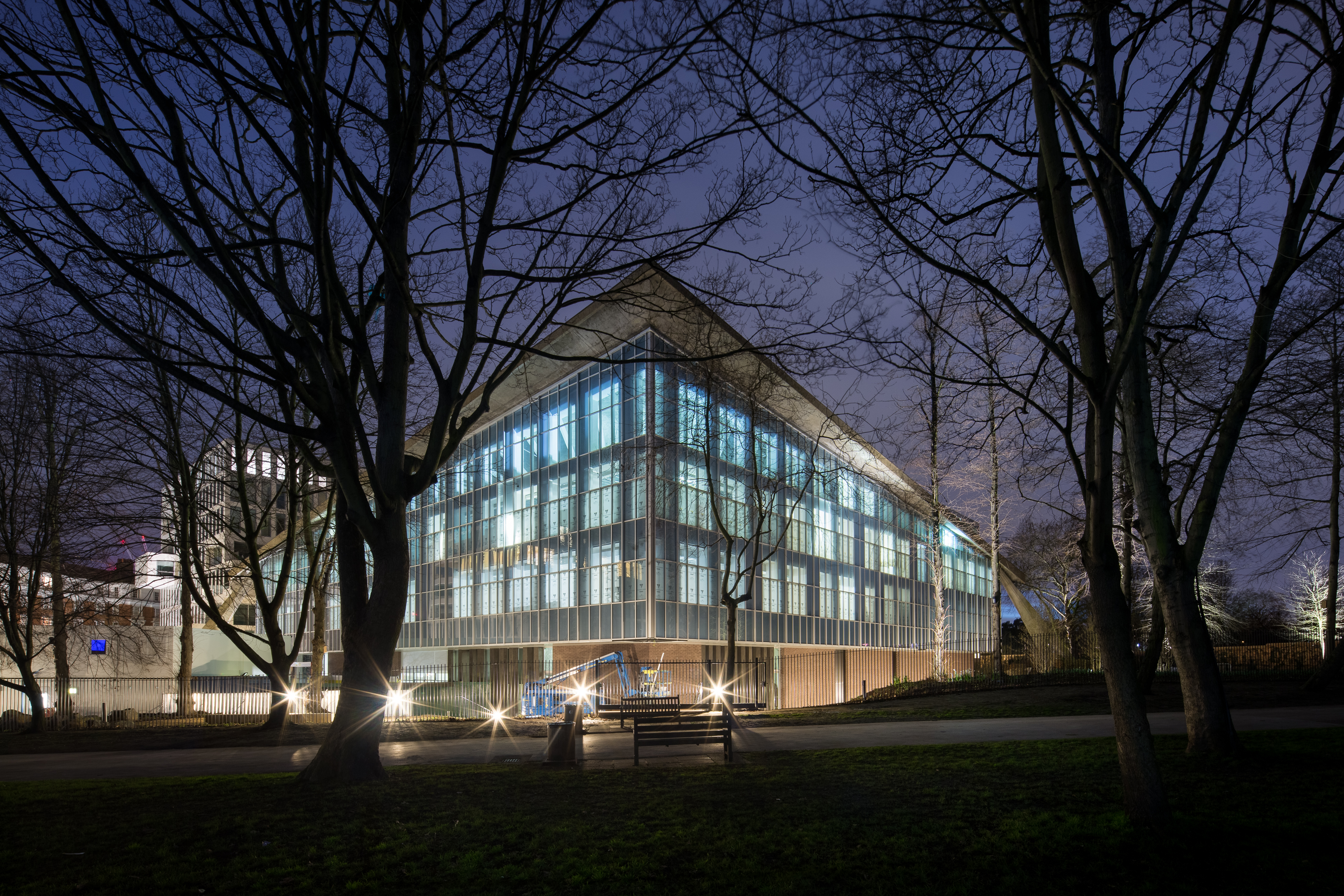 An angular glass and concrete building is lit up, at night, surrounded by trees.