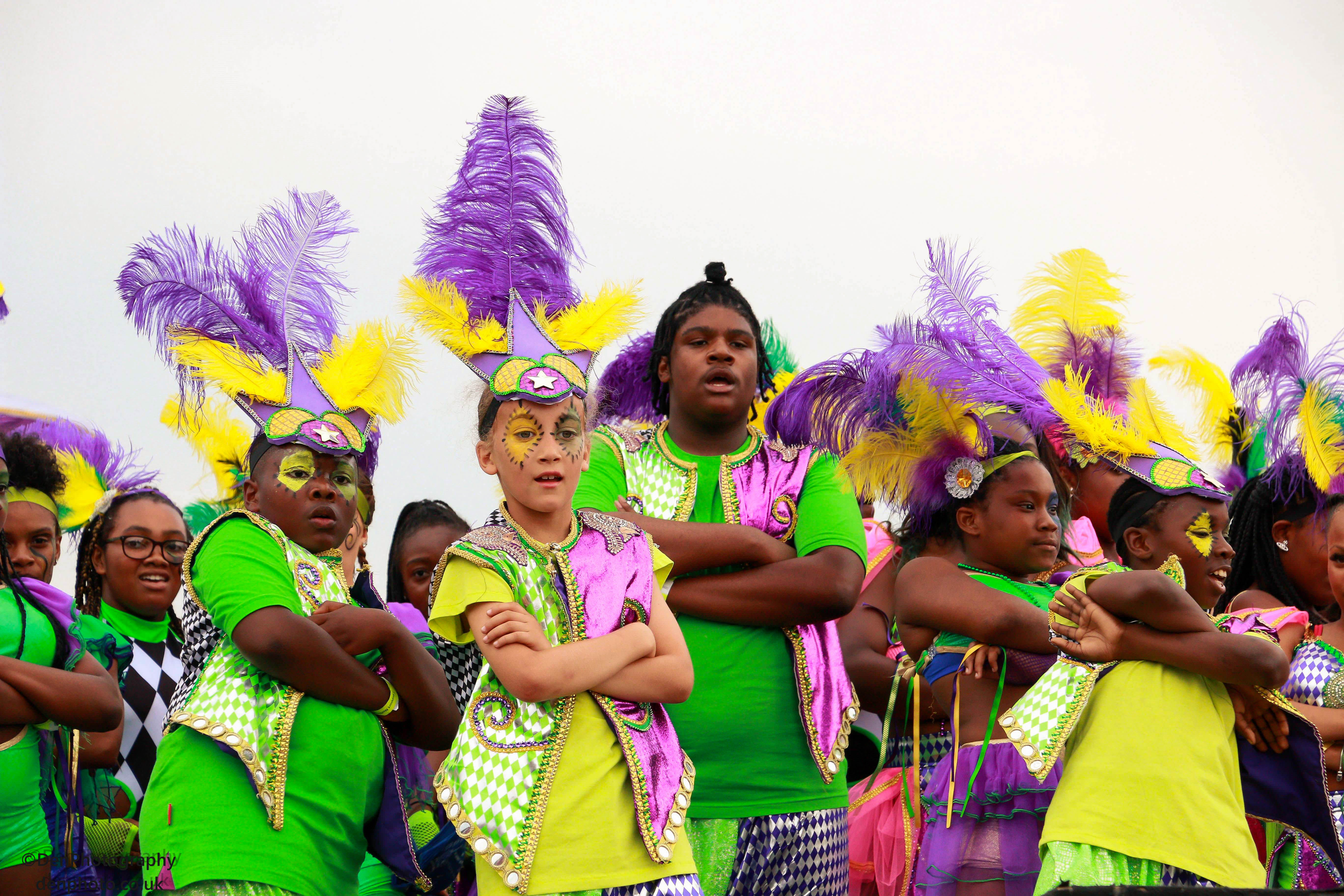 A group of young people perform in bright carnival costumes and purple and yellow headdresses