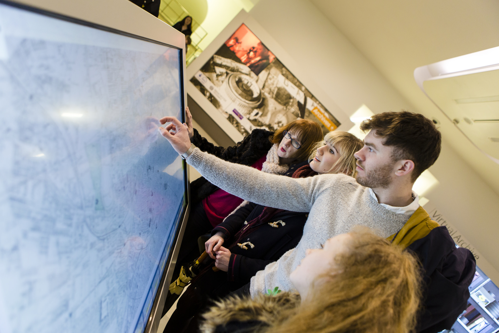 A group of people gather round an interactive screen in Manchester Central library.
