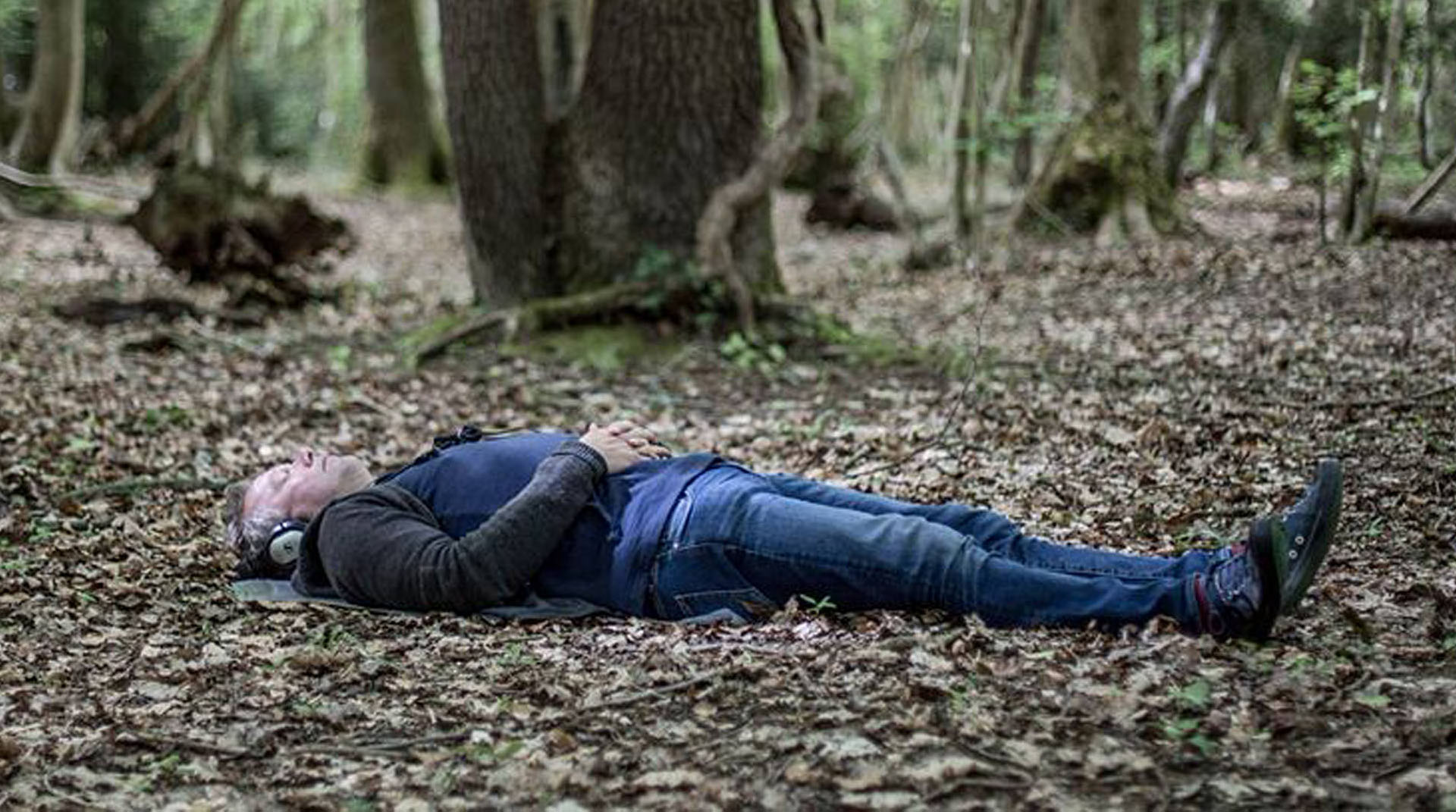 A man lies in a forest while listening to headphones.