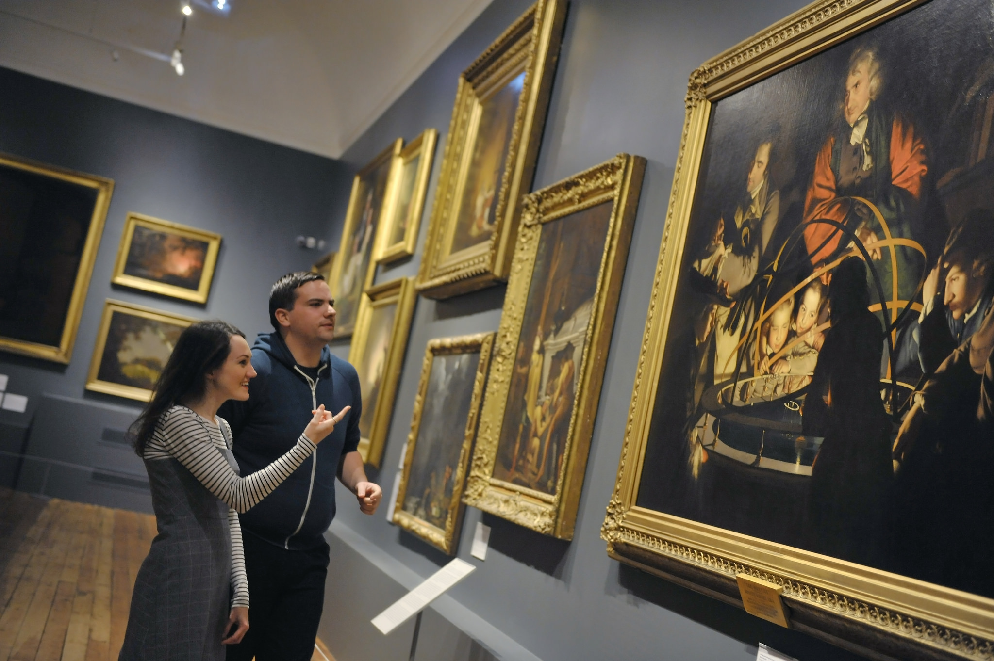 Two people look at a painting in a gallery.