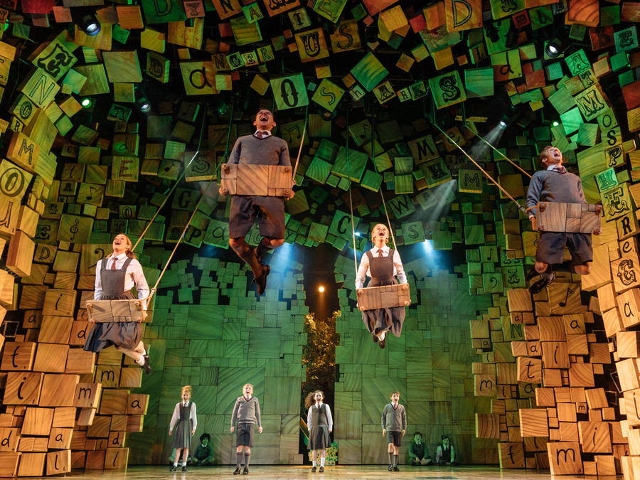 A group of children perform onstage in school uniforms, as part of RSC's Matilda the Musical. Four swing on wooden swings, suspended in the air.