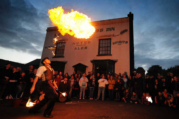 An actor dressed in period costume juggles fire in front of a crowd, outside the pub at the Black Country Living Museum