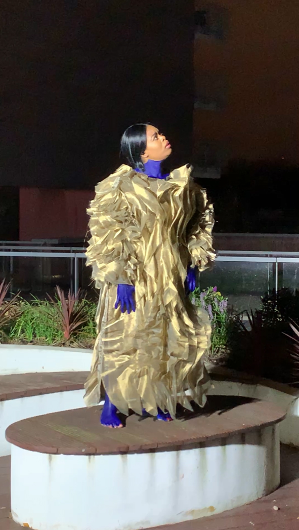 A person dressed in a costume of gold lamé and electric blue body paint designed by Osman Yousefzada
