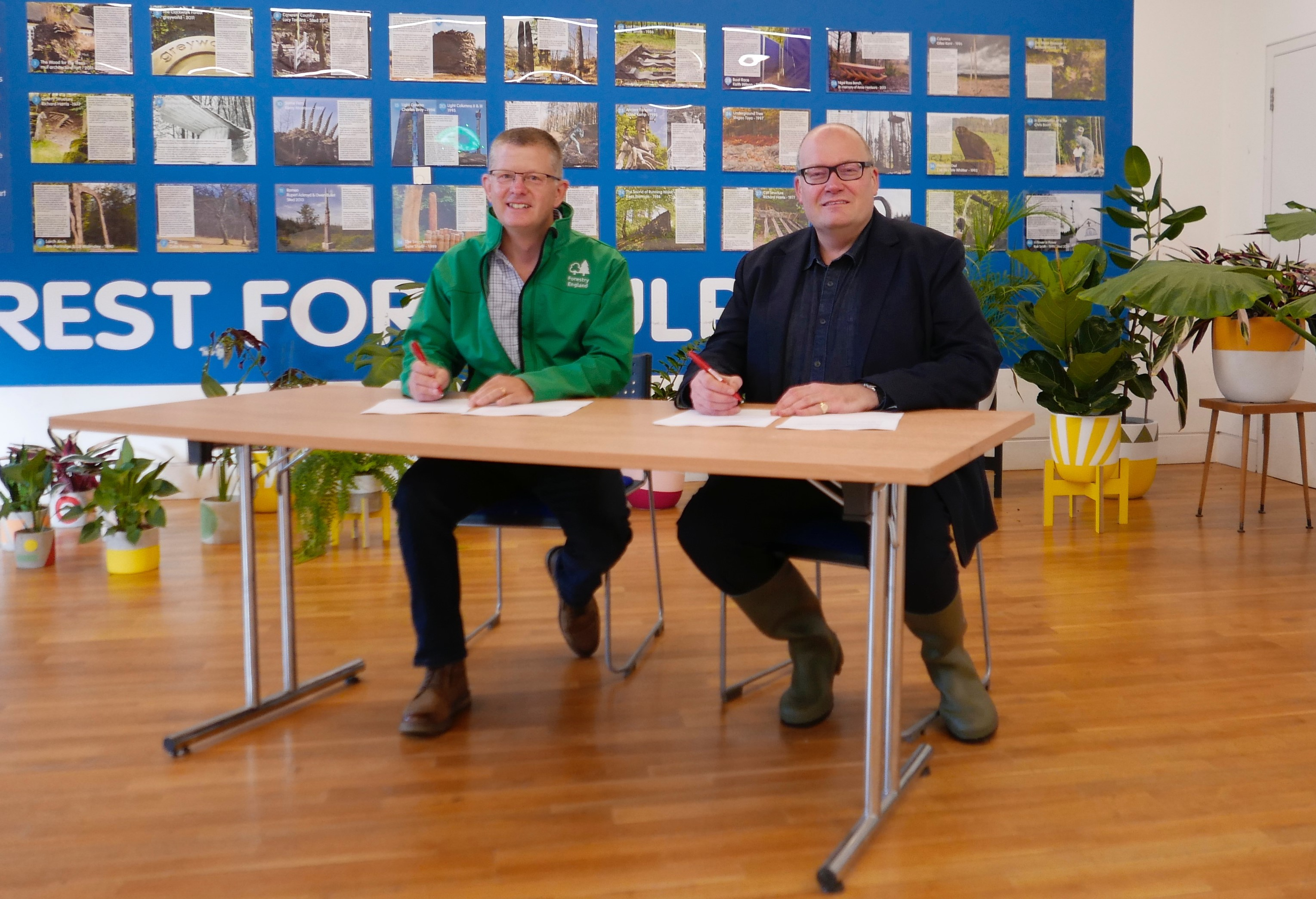 A photograph of Mike Seddon and Darren Henley sat at a table. They are smiling, and each hold a pen - suggesting they have just signed a document.
