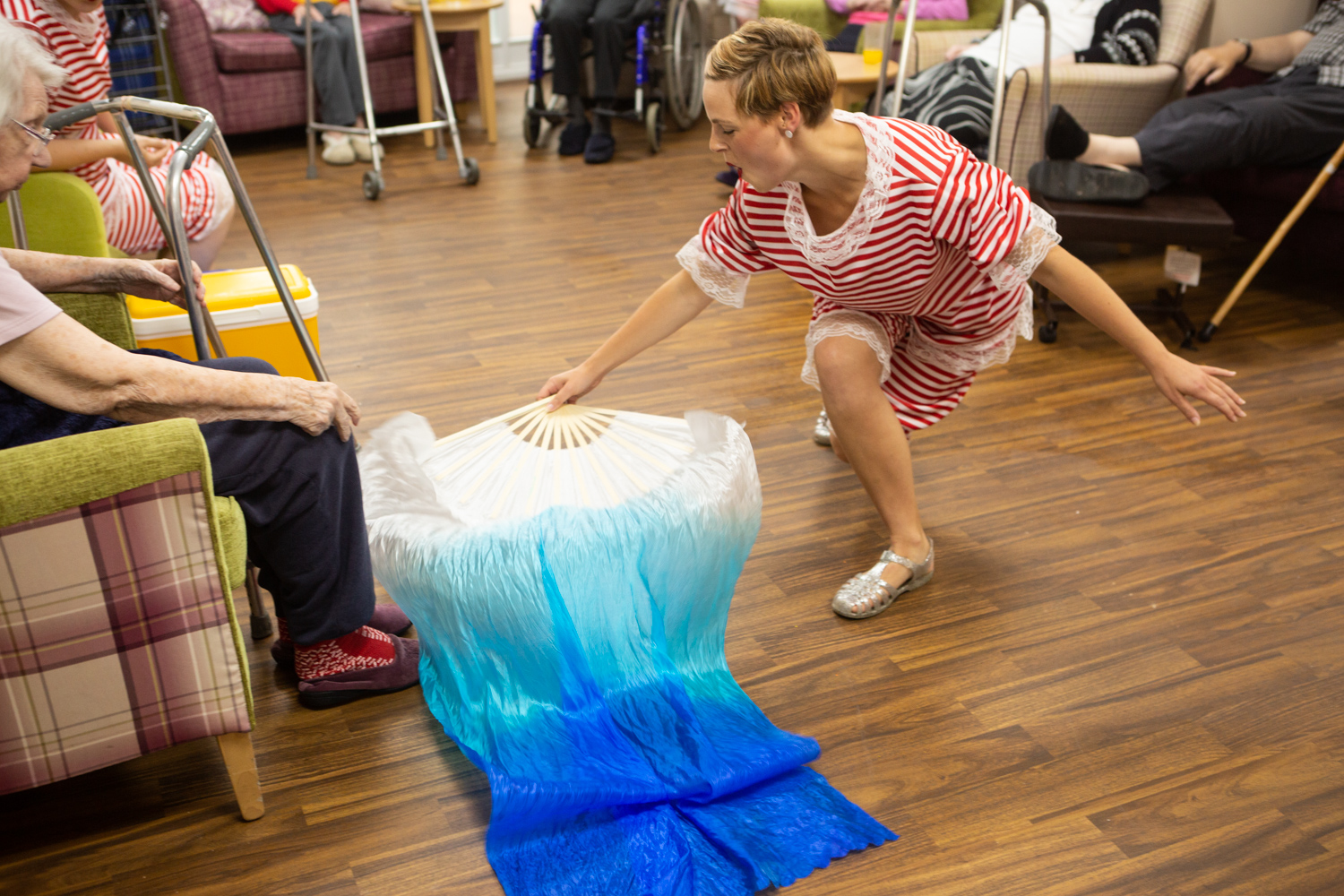 A performer with a blue silk fan trails it along the floor in front of a care home resident