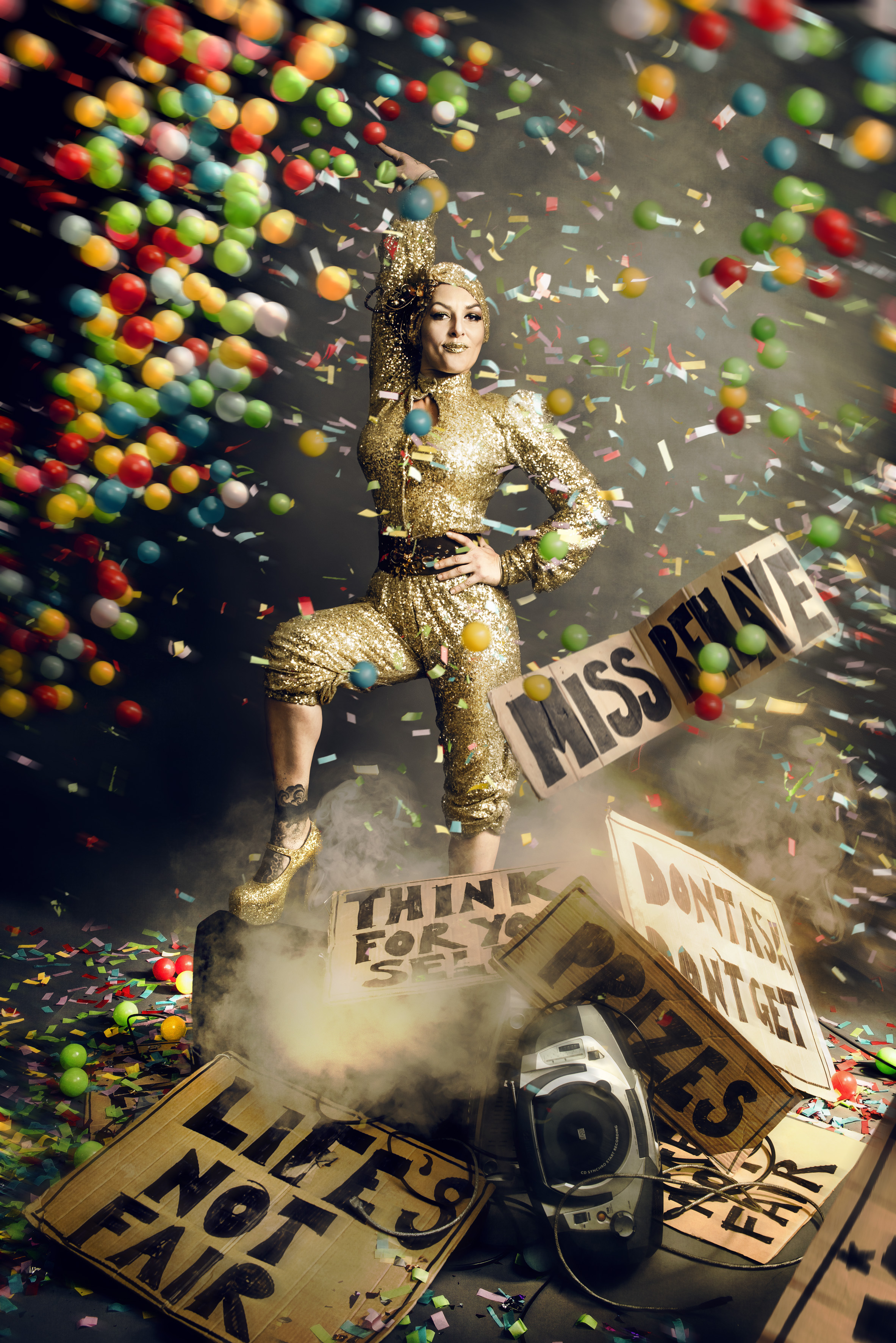 Miss Behave dressed in a shiny jumpsuit, with lots of multi-coloured balls and confetti falling around her.