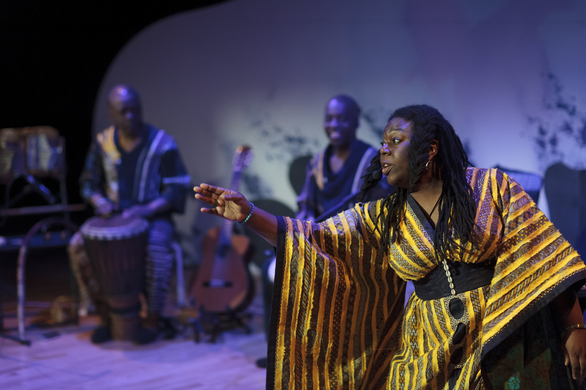A woman in African dress reaches out across a stage in front of musicians.