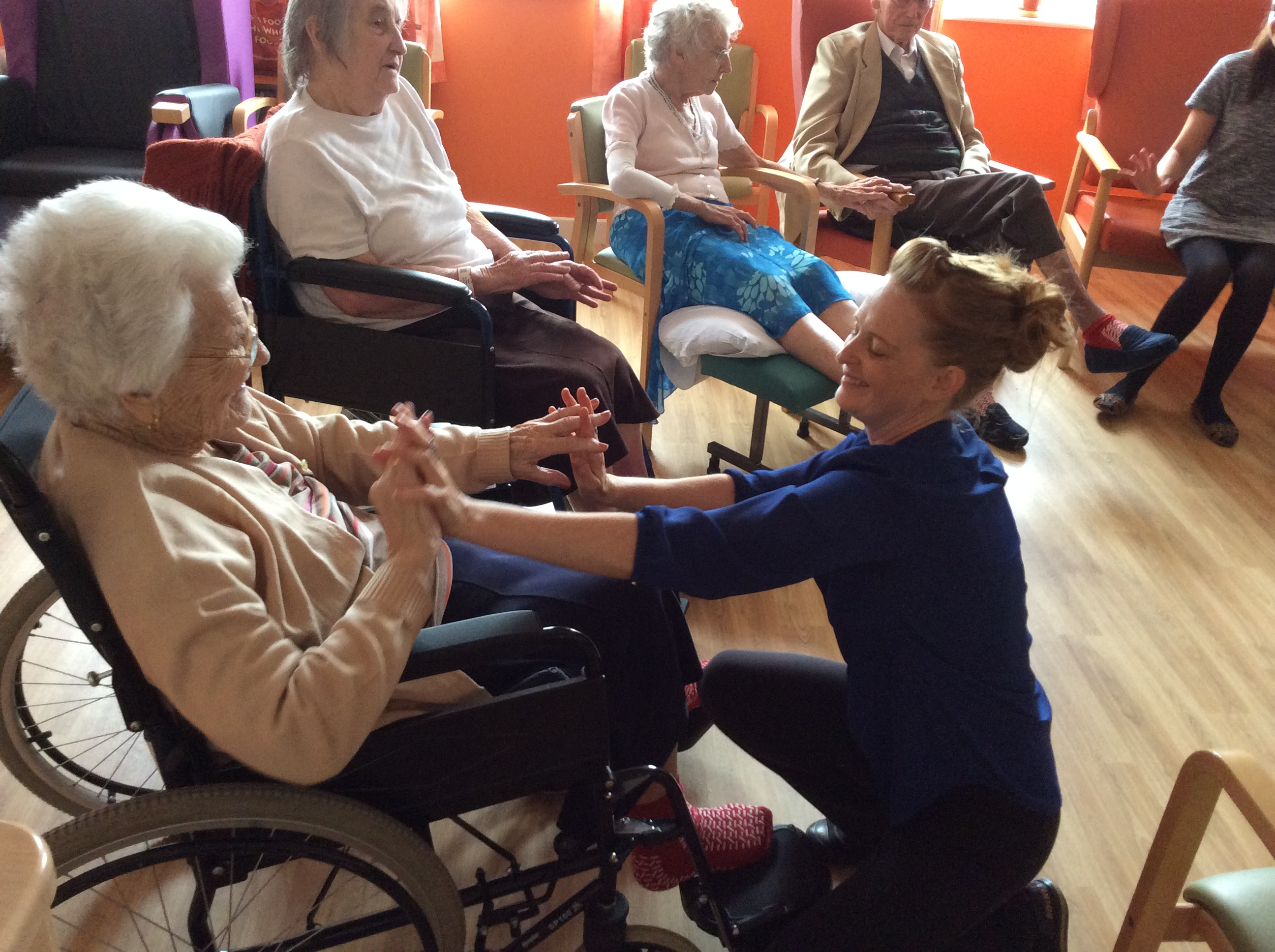 An elderly wheelchair user touches hands with an arts worker. Three other elderly people are visible in the background.
