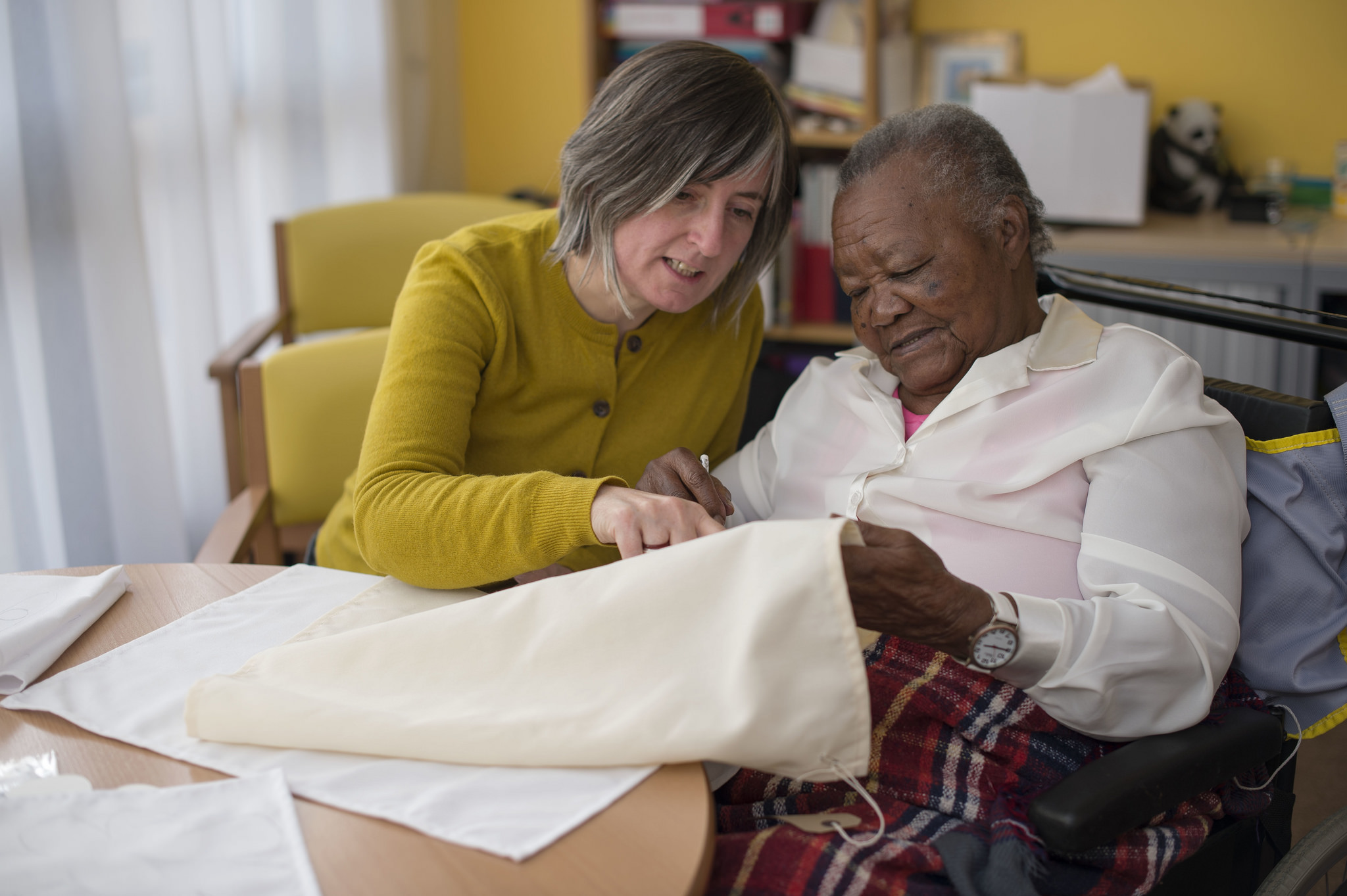 An elderly lady studies a large fabric napkin with the help of artist Deirdre Nelson.