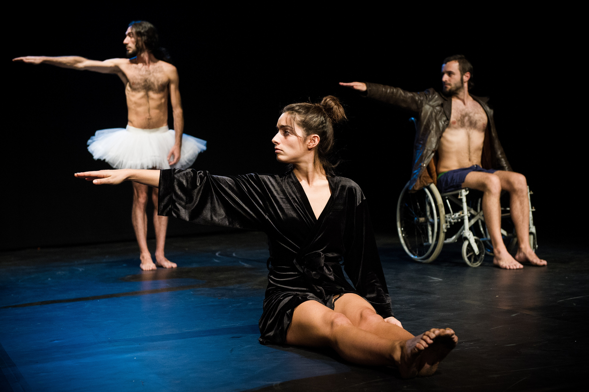 Three dancers pose with their right arms outstretched. One is standing, one is seated on the stage floor, and one is a wheelchair user.