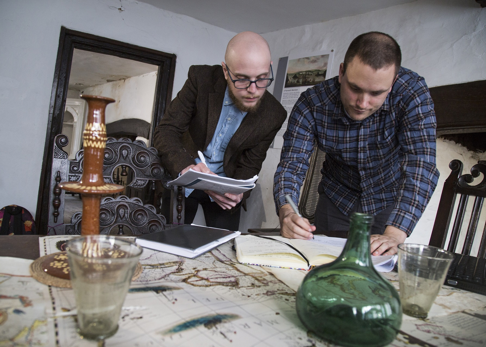 Two writers lean over a table in an old-fashioned house, making and comparing notes.