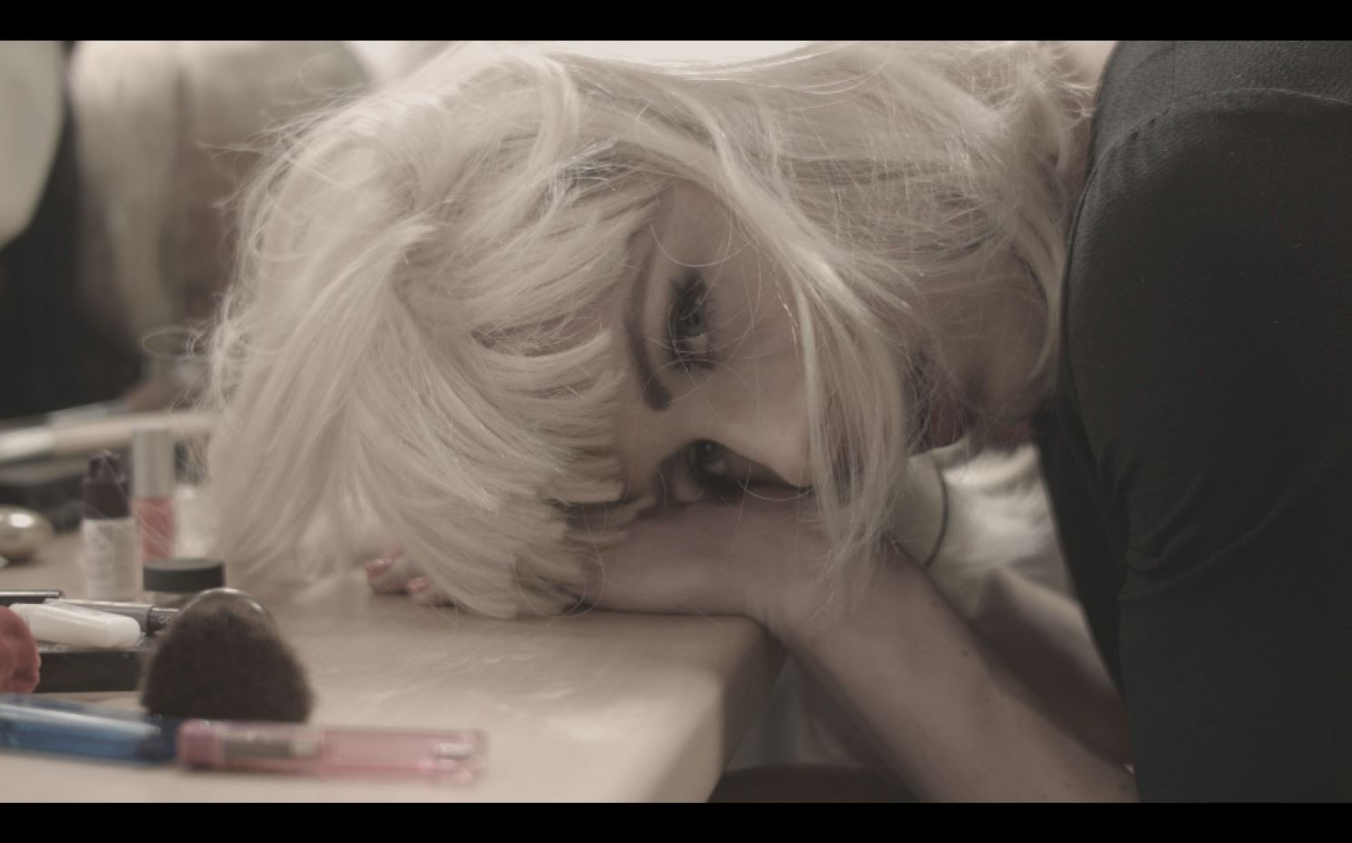 A young woman in a platinum blonde wig rests her head on a desk