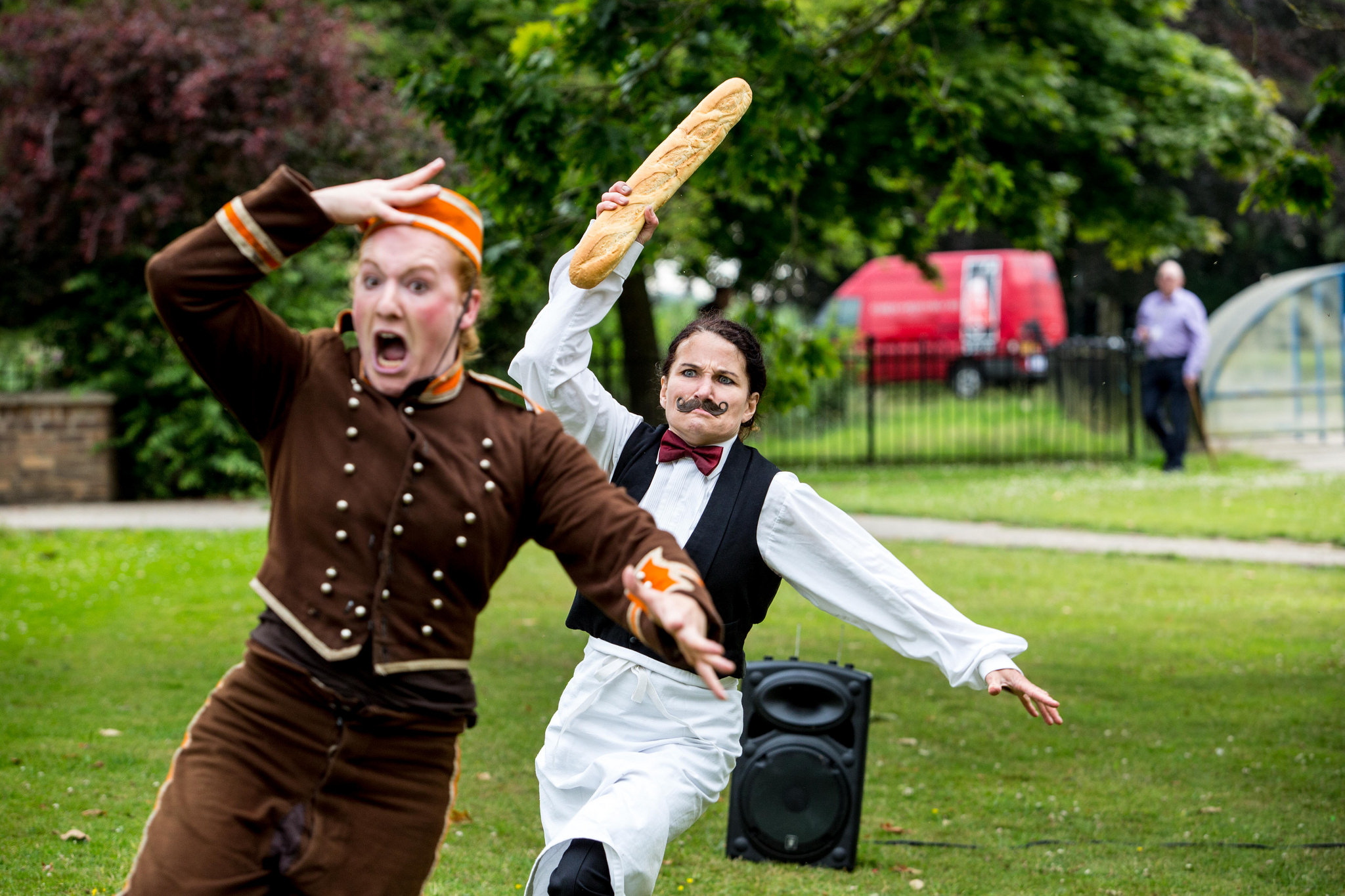 A performer dressed as a bellboy is chased by another dressed as a waiter, wielding a baguette, as they run across a lawn.