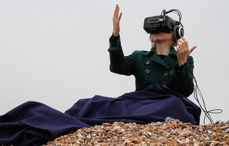 A woman sits on a pebbled beach wearing a virtual reality headset