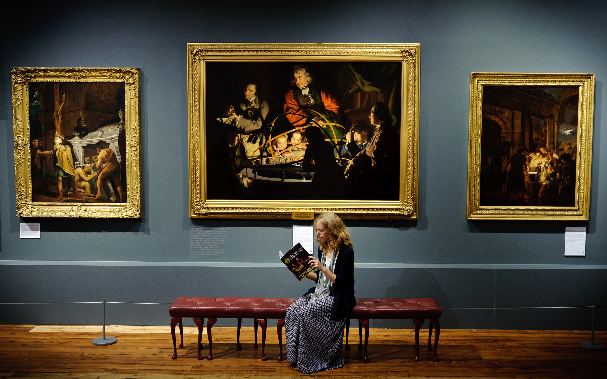 A lady reads a guidebook in front of three elegant paintings in a gallery space.