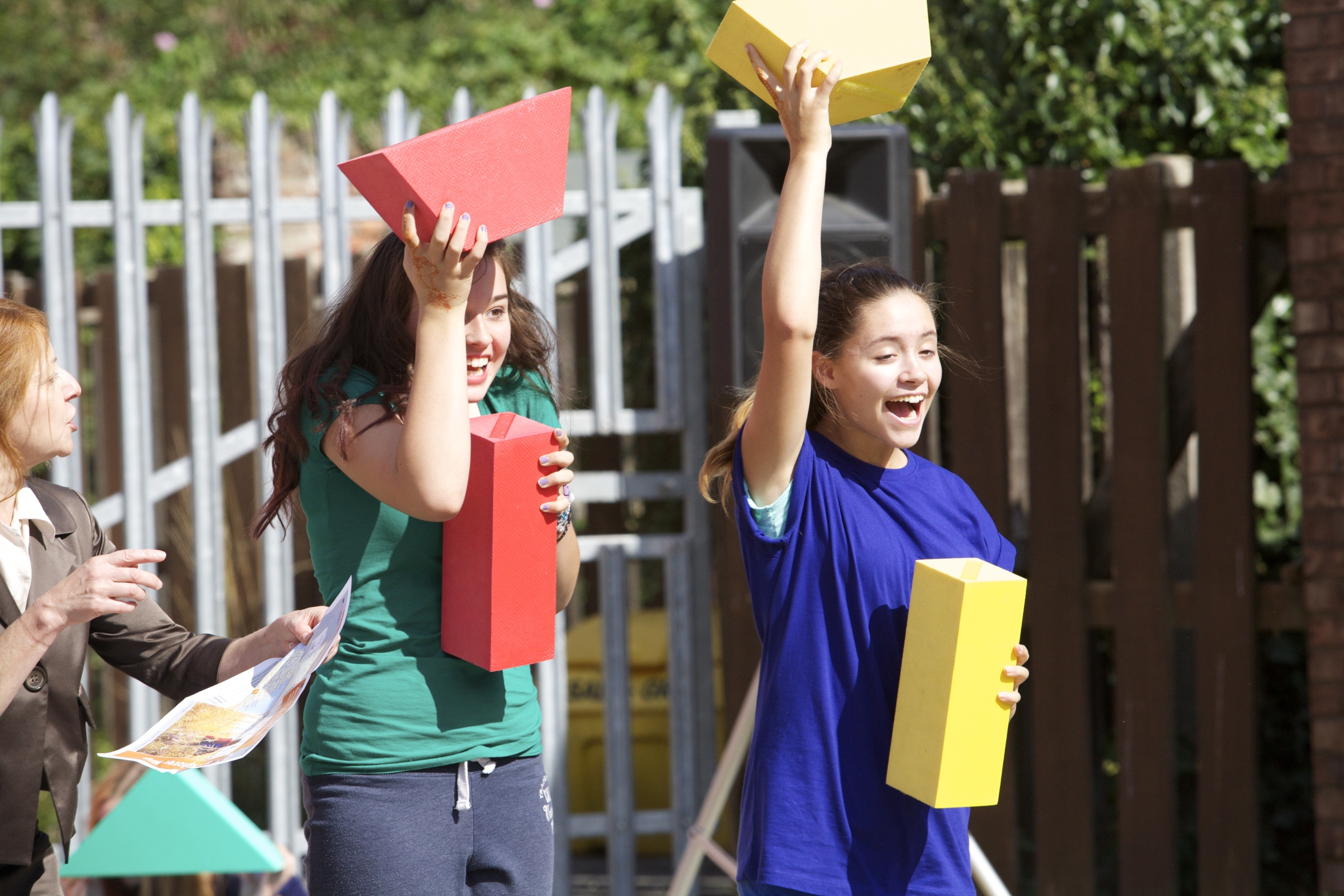 Two girls hold large shape blocks above their heads.
