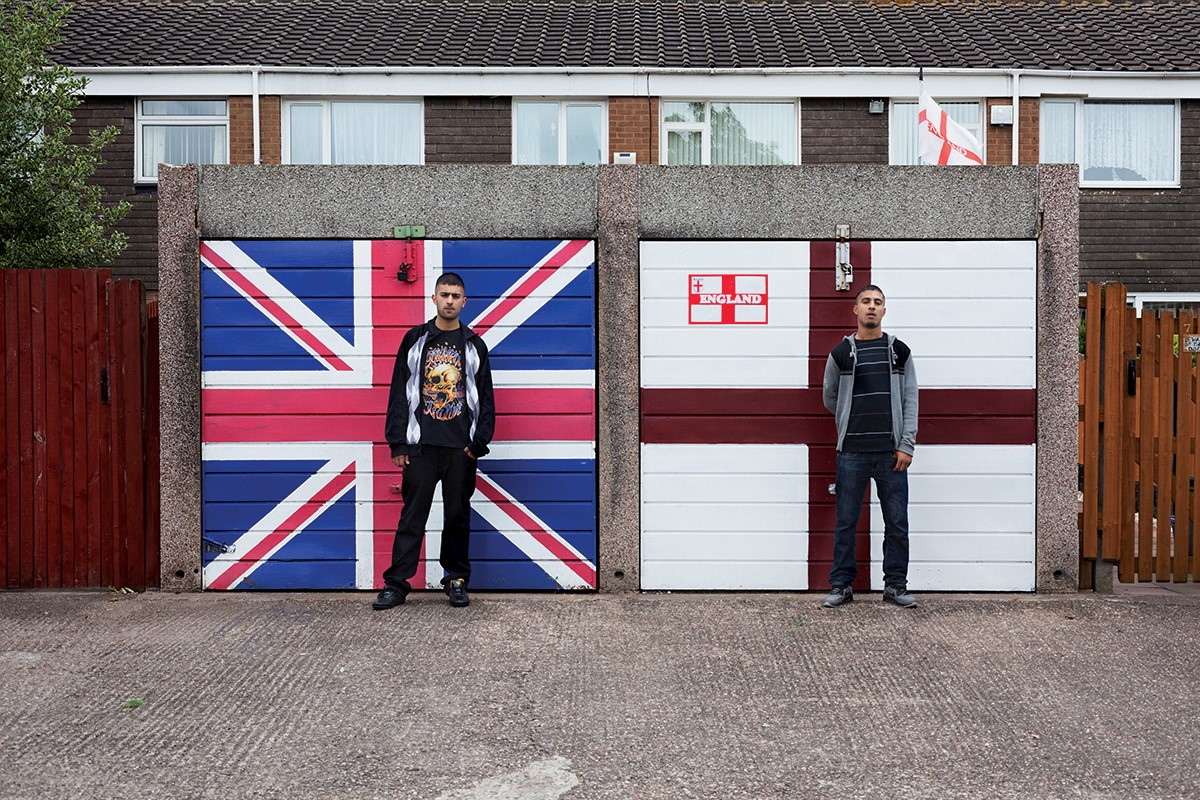 Two Asian men stand in front of garage doors painted with the English and Great British flags